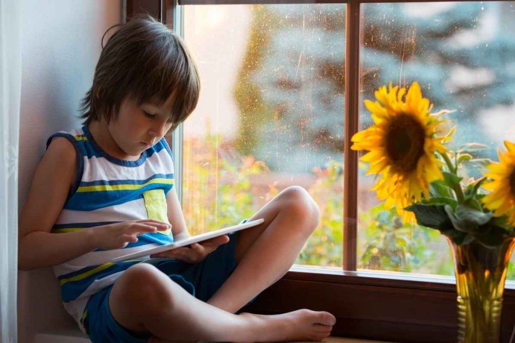 child using a Learning Apps on tablet by a window at home